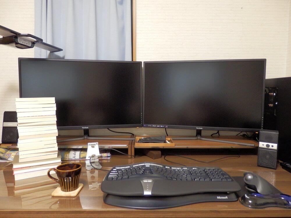机の上にデスクトップパソコンと小説と飲みかけのコーヒーカップが置かれている