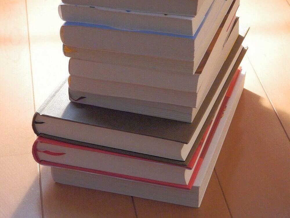 積み重ねた本に後ろから淡い光があたってる