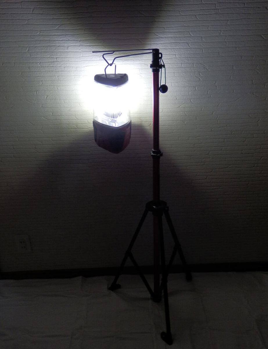 ロゴスのランタンポールに掛かった、点灯中のコールマンのLEDランタン