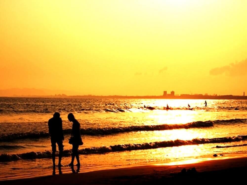 海辺で夕陽を浴びながらデートを楽しむ恋人同士