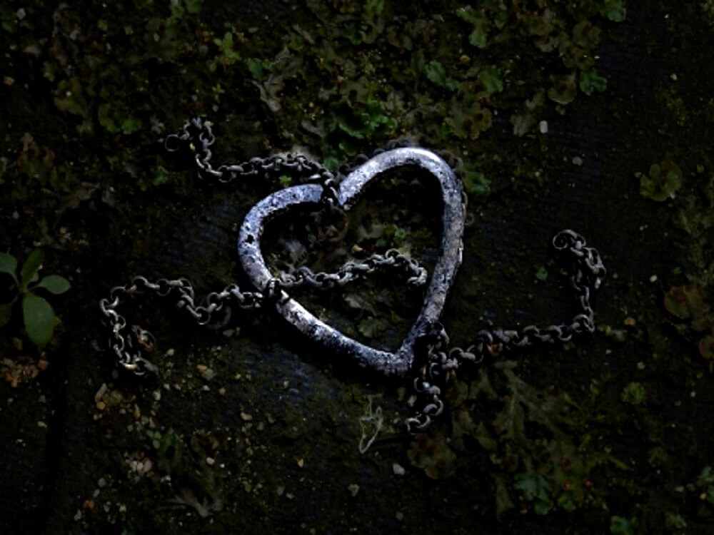 ボロボロのハートのネックレスが地面に落ちている画像