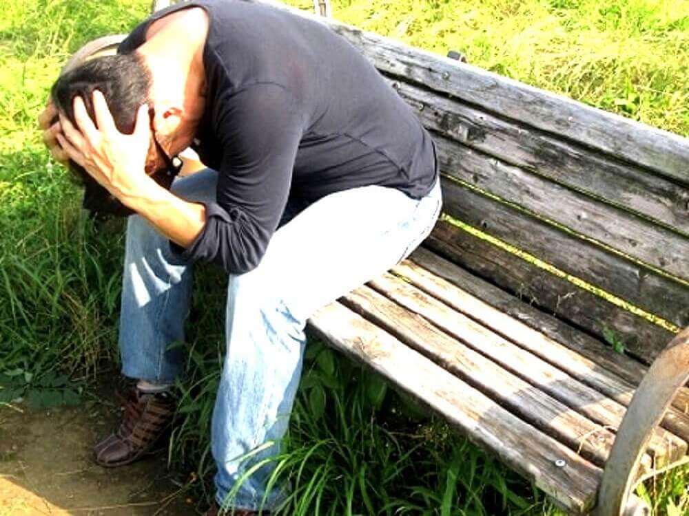 ベンチに座って頭を抱えて悩んでいる男性