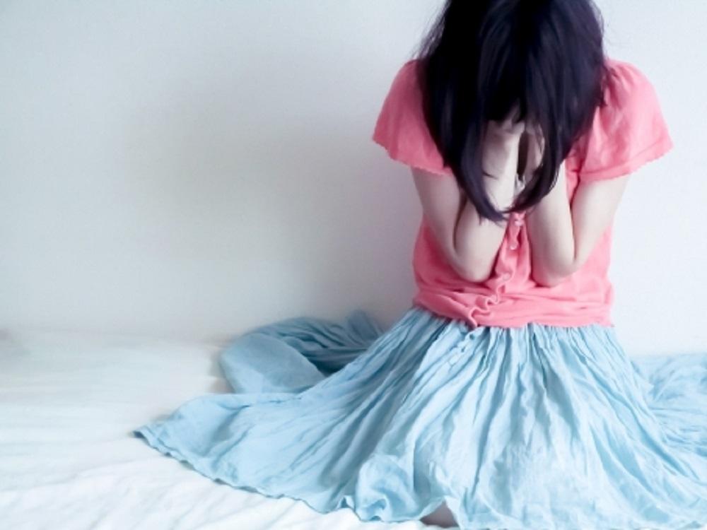 座り込んで顔を抑えて泣いている女性