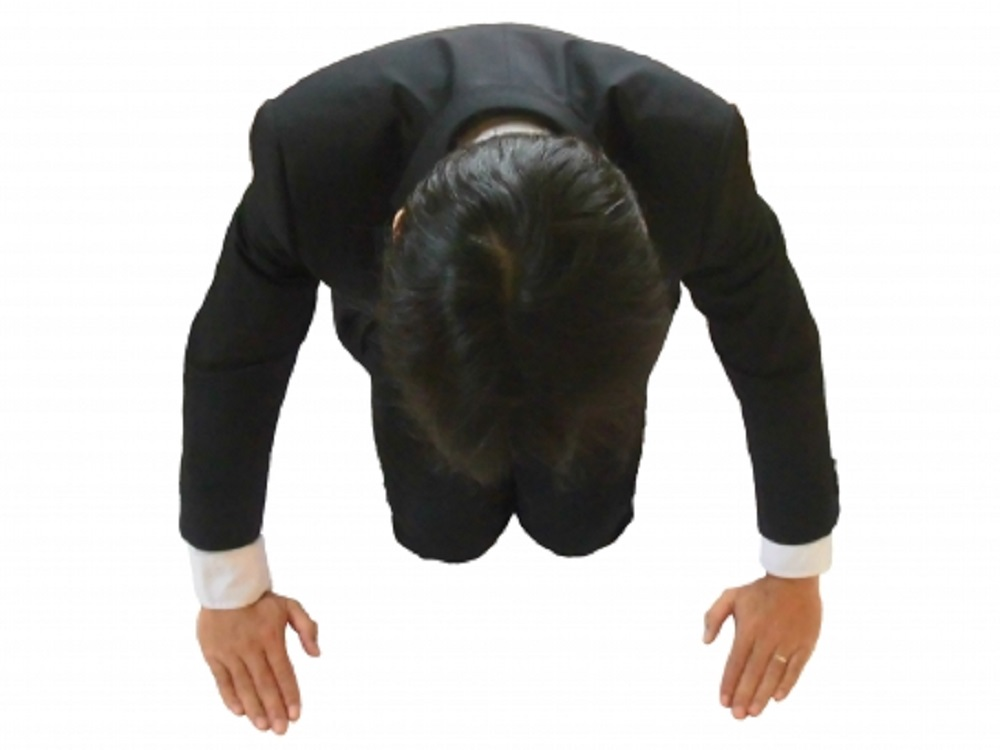 スーツ姿の男性が謝罪している