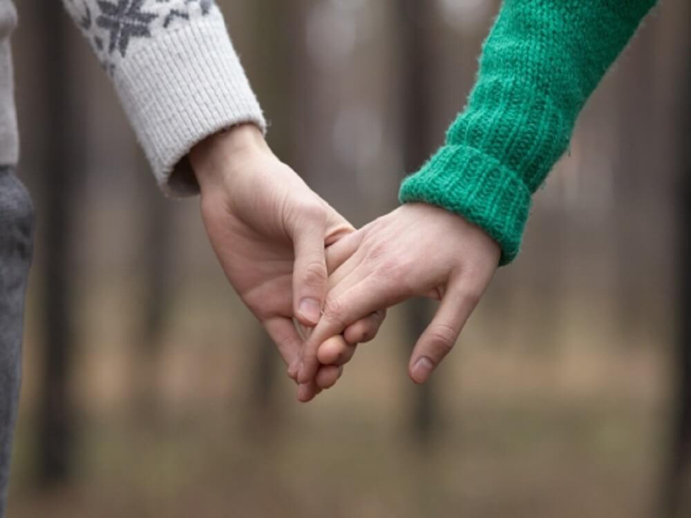 セーターを着た男女が仲良く手をつないだ画像