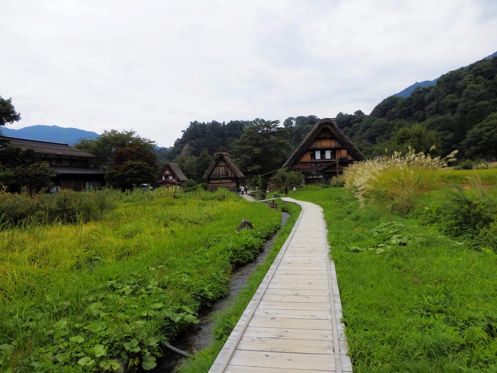 白川郷合掌村のかやぶき屋根の建造物と板張りの小道
