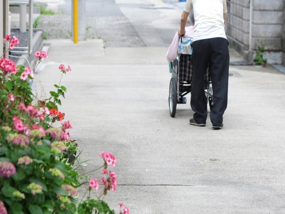 老婆の乗った車いすを夫が押している画像