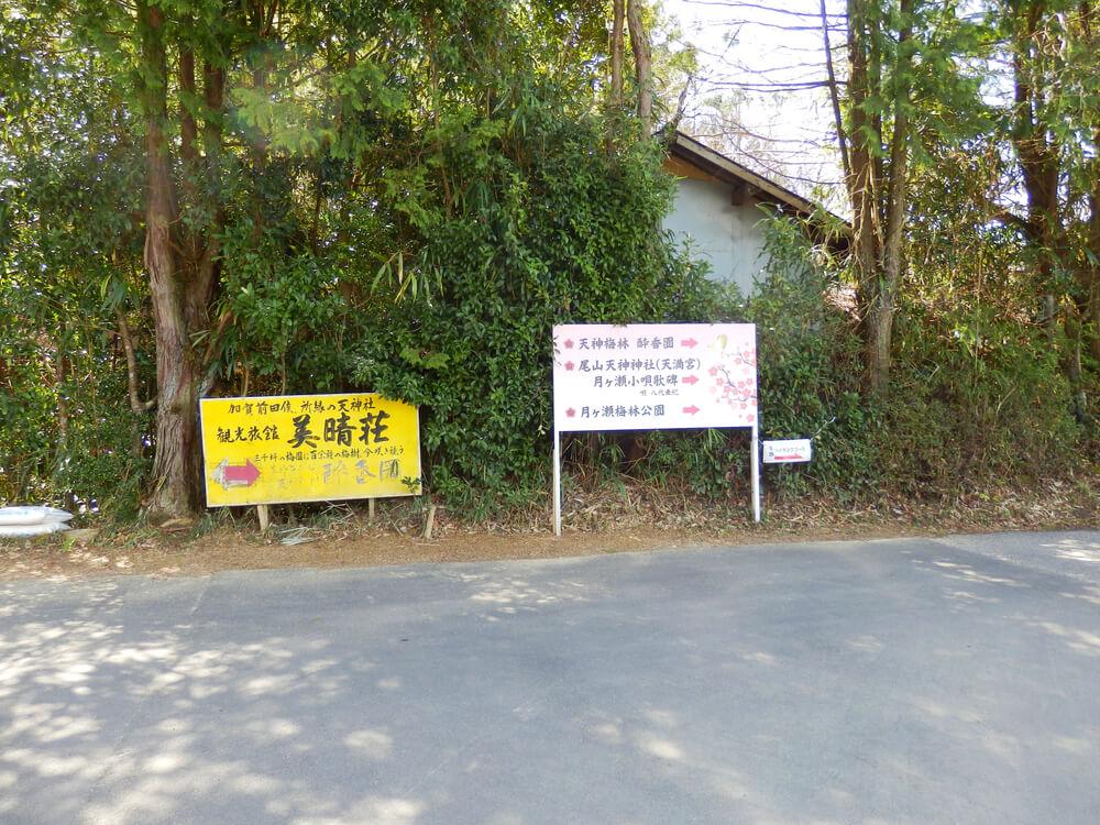 右に行くと天神梅林・酔香園・尾山天神神社・月ヶ瀬小唄歌碑・月ヶ瀬梅林公園、左に行くと梅林公園入口と書かれた立て札の画像