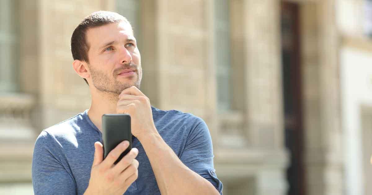 スマートフォンを持ち、承認欲求について考える男性