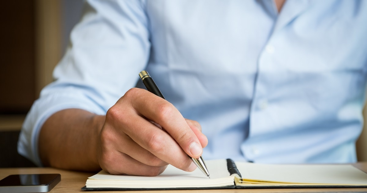 気づきをノートに記録するビジネスパーソン