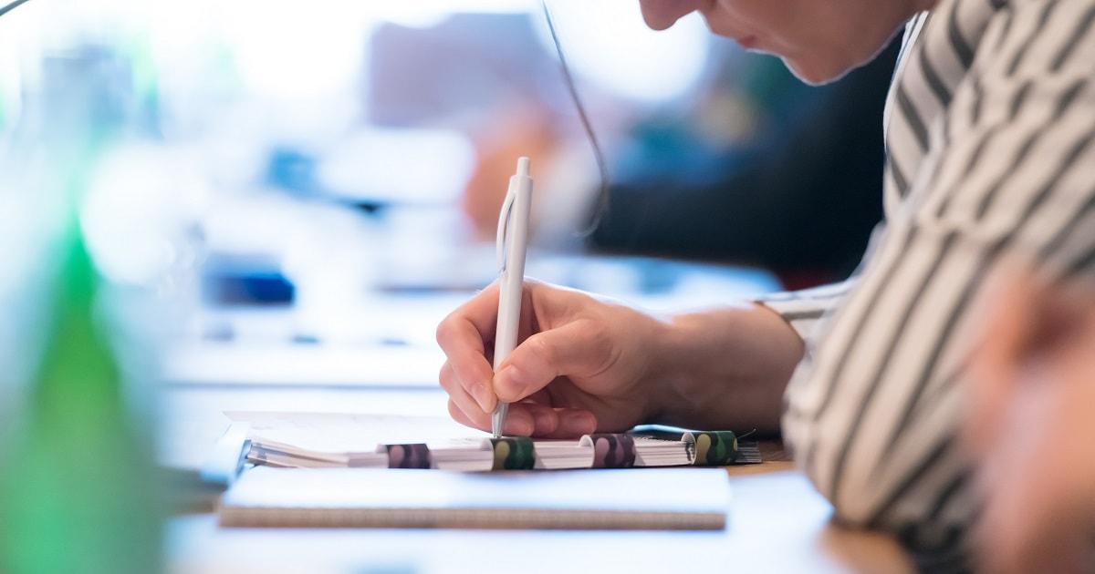 セミナーに参加し手書きで記録するビジネスパーソン