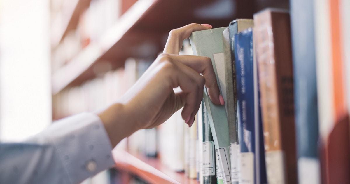 知的好奇心を持って本を探す手