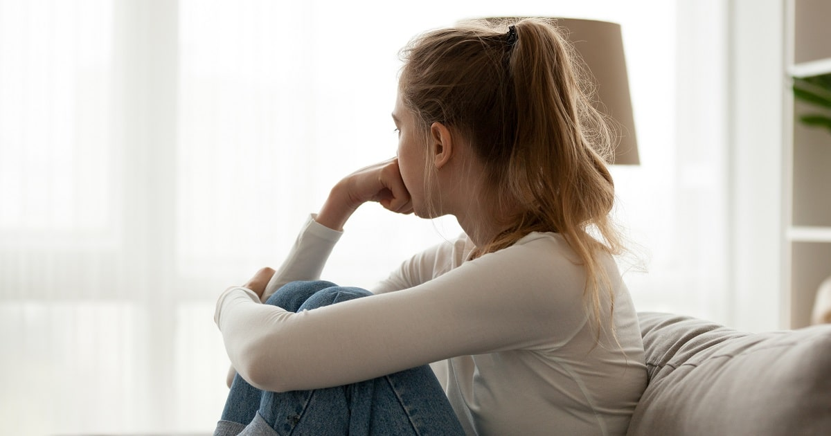 不安いっぱいの膝を抱えた女性