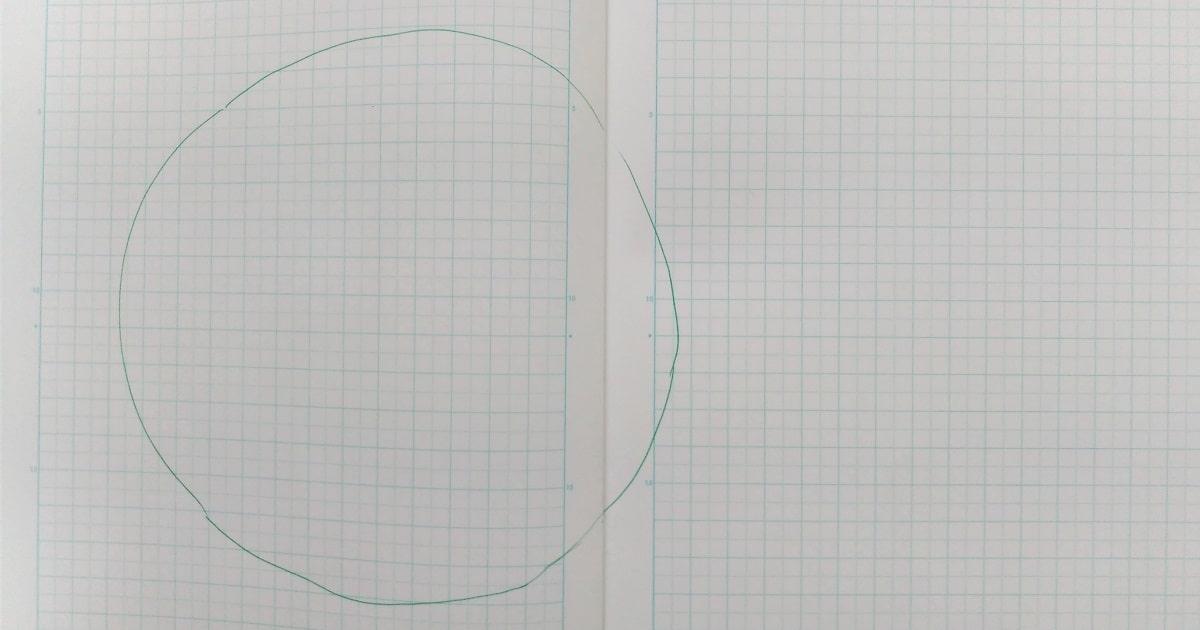方眼ノートを見開き、メインテーマのための円を中央から少し左にずらして描く