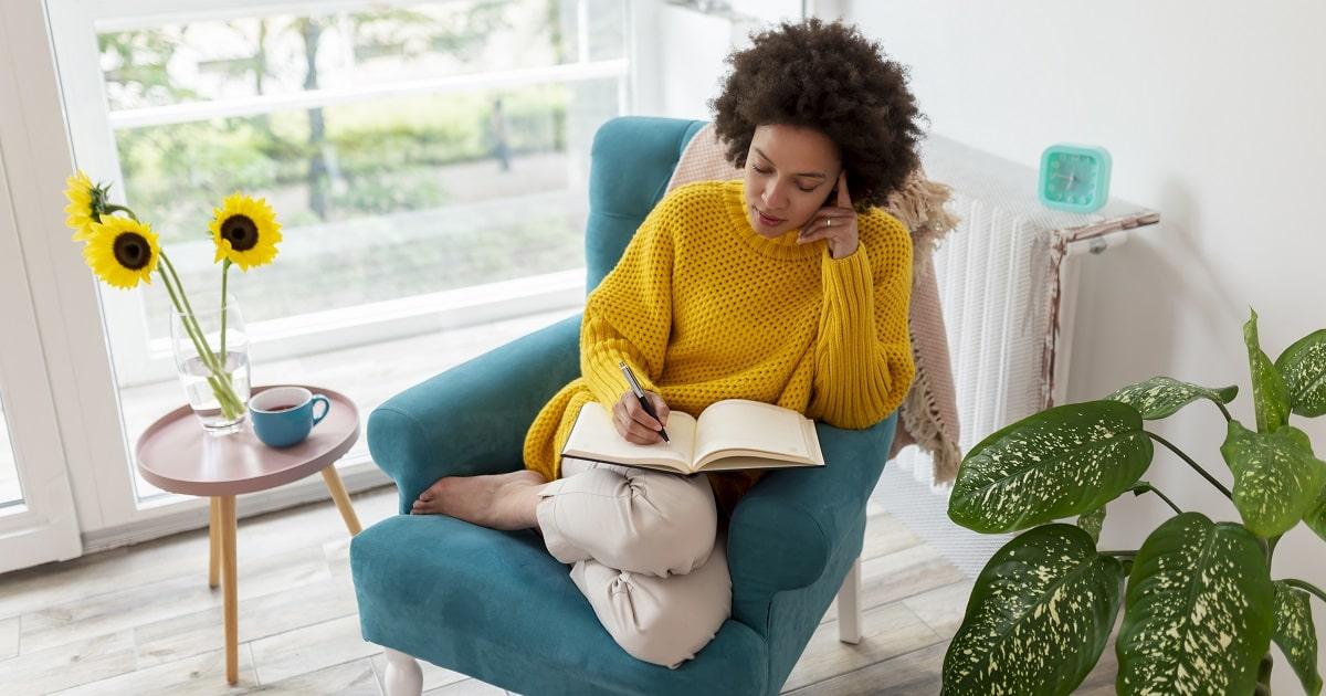朝、リラックスしながら3行日記を書く女性