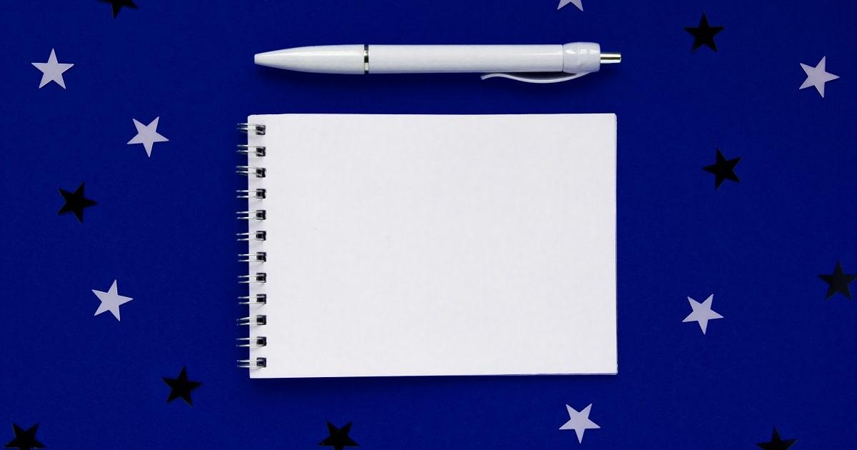 星のイラストを背景にしたメモ帳。就寝前に書く3行ポジティブ日記のイメージ
