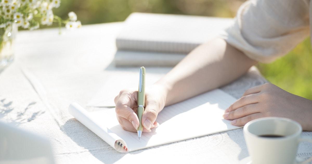 コーヒーを飲んでくつろぎながら自分への手紙を書く女性
