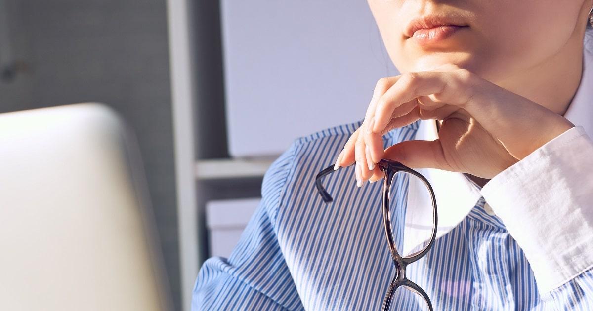 いったん思いとどまり、メガネを外して考えるビジネスパーソン