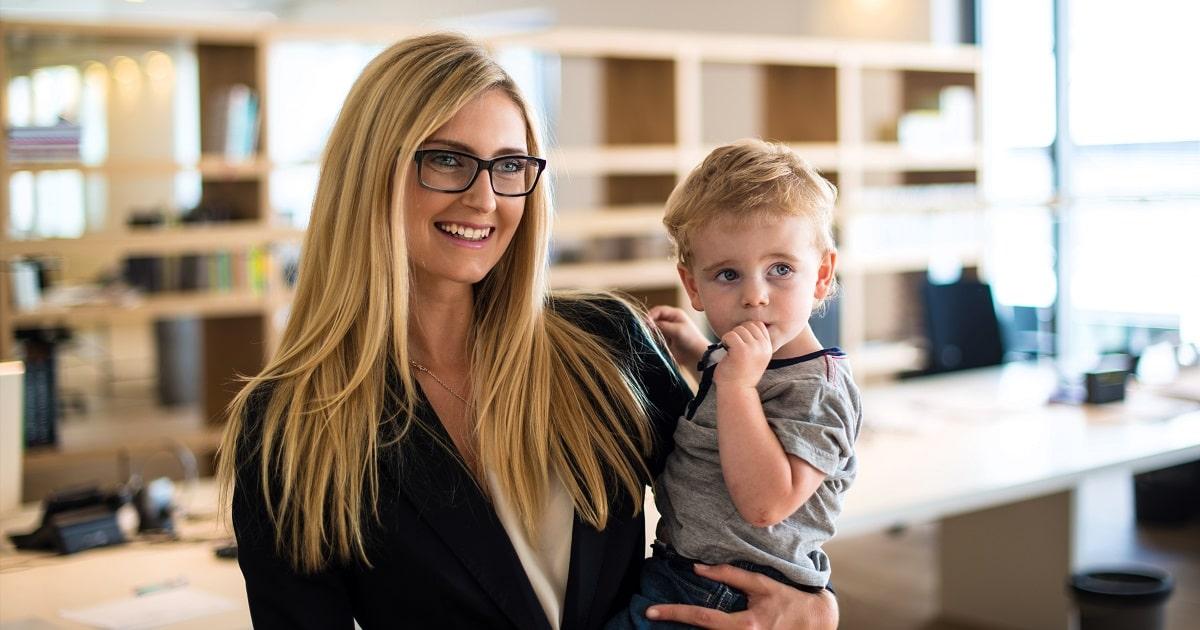 小さな子どもを抱っこする素敵なビジネスパーソン(女性)