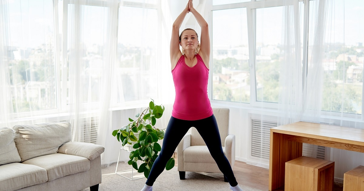 家で挙手跳躍運動(ジャンピングジャック)をする女性