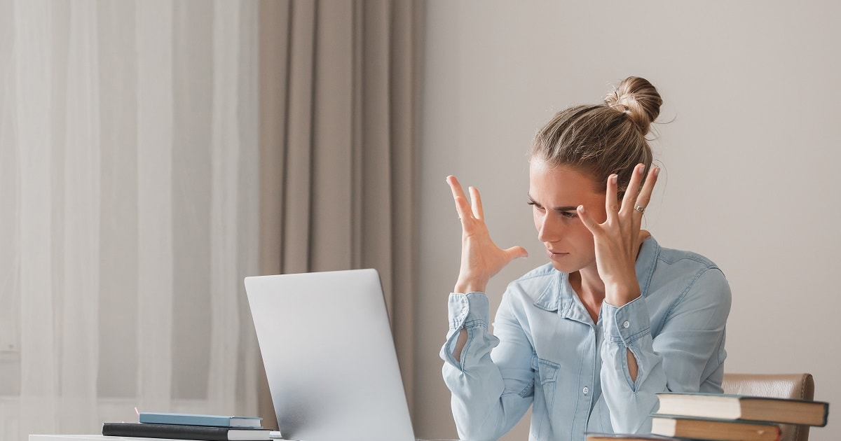 ノートパソコンを前に、怒りを覚えている女性