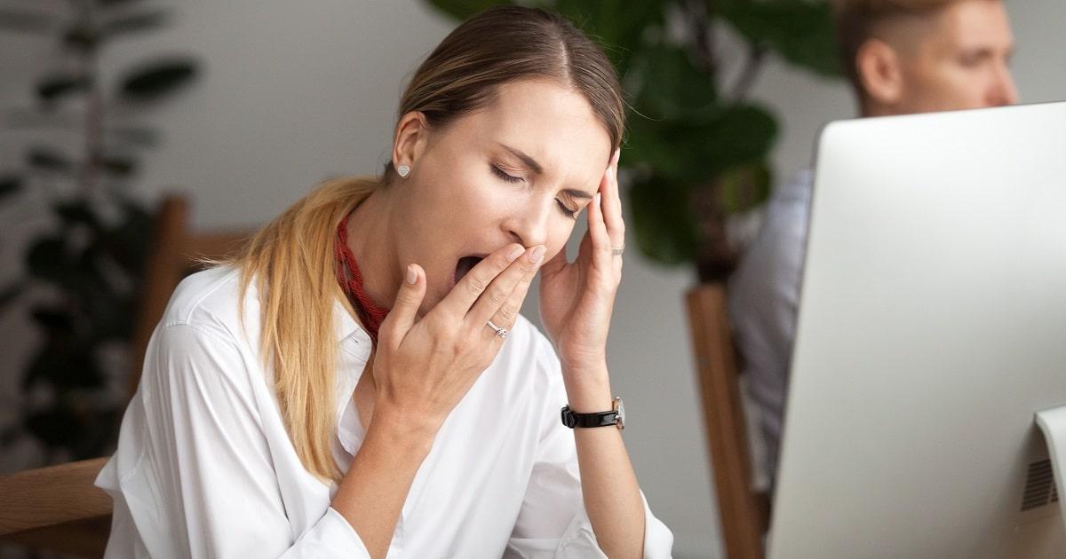 仕事中、眠そうにあくびをする女性