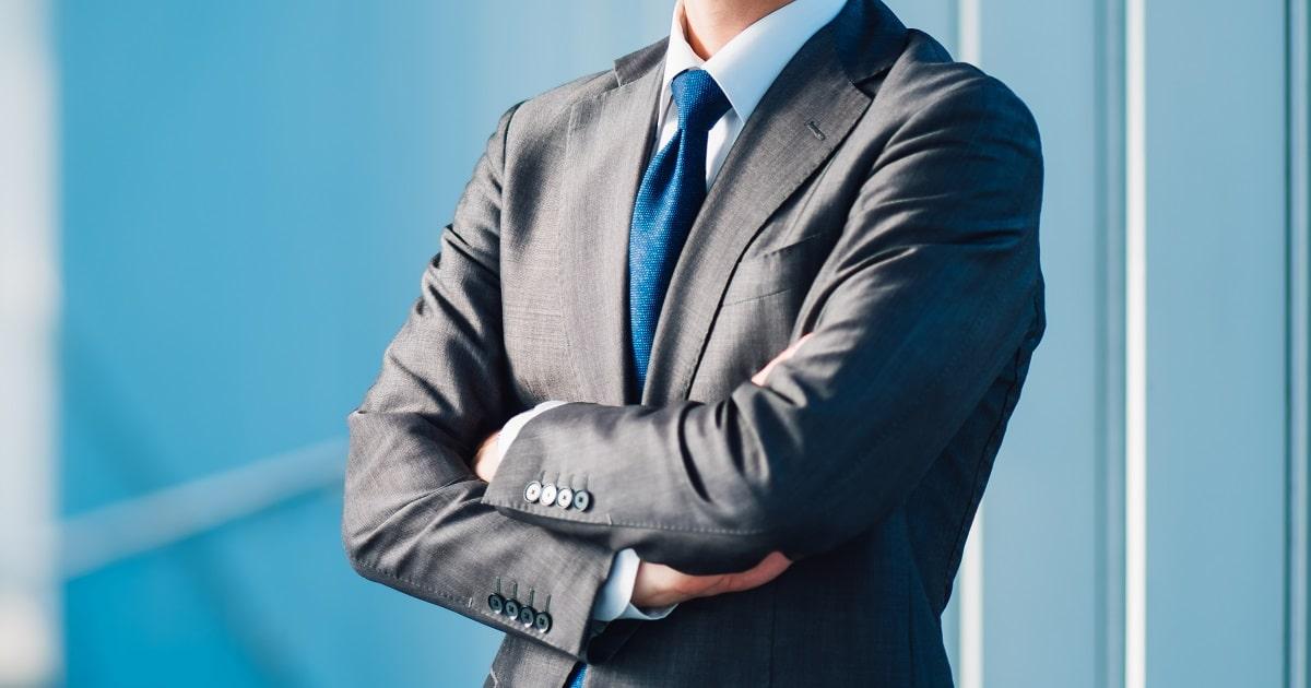 自信に満ちあふれたスーツ姿・青いネクタイのビジネスパーソン
