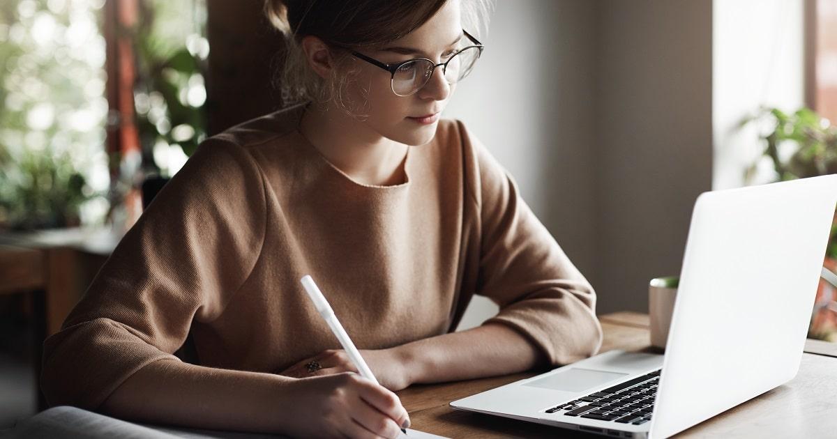 ノートブックパソコンを見ながら何かをメモするビジネスパーソン