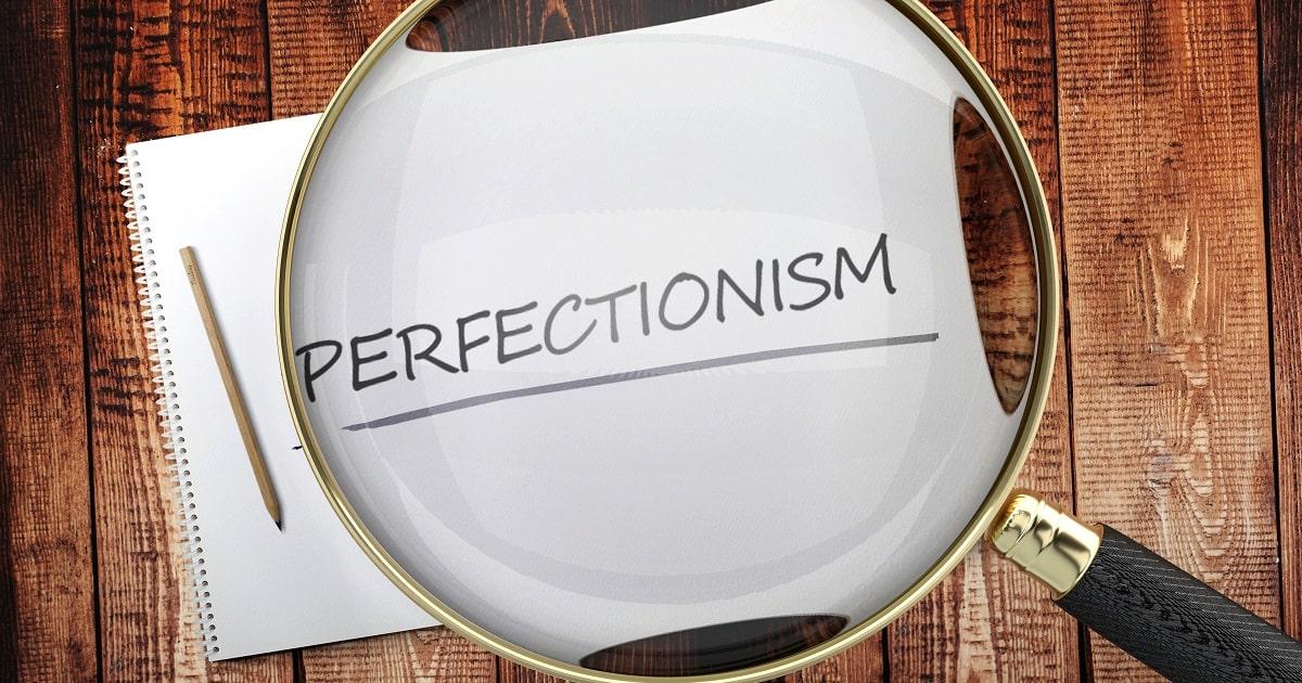 完璧主義を探求する・虫眼鏡で「perfectionism」の文字を眺めている画像