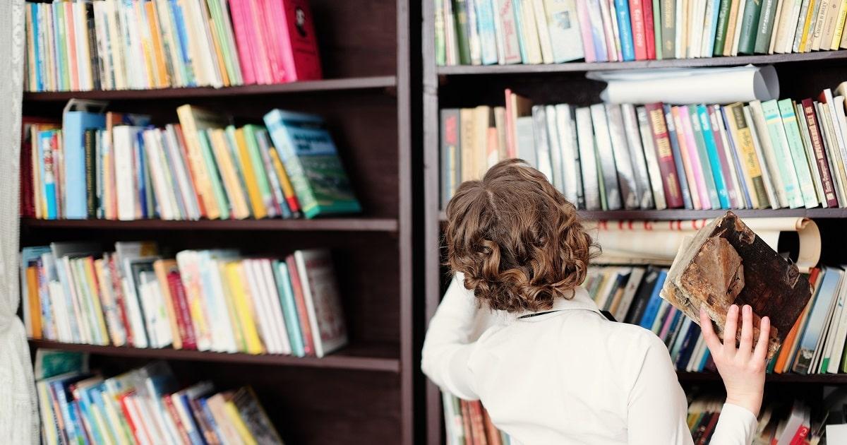 本を手に、多様な考えや情報に到達せんとしている女性