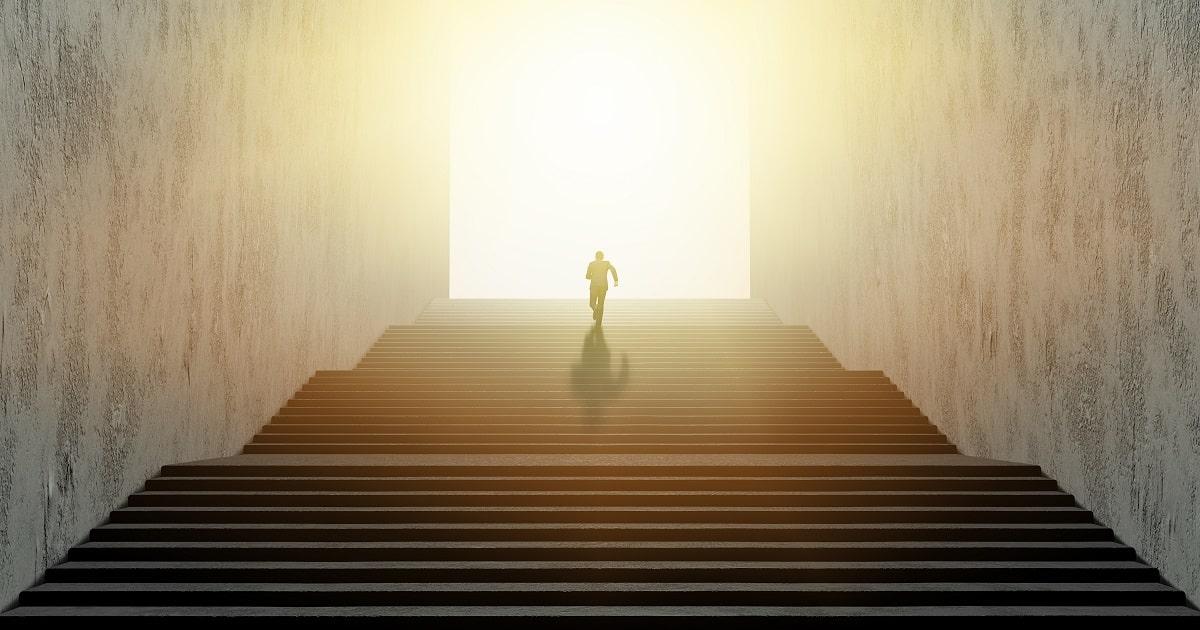 階段を駆け上っていくビジネスパーソン