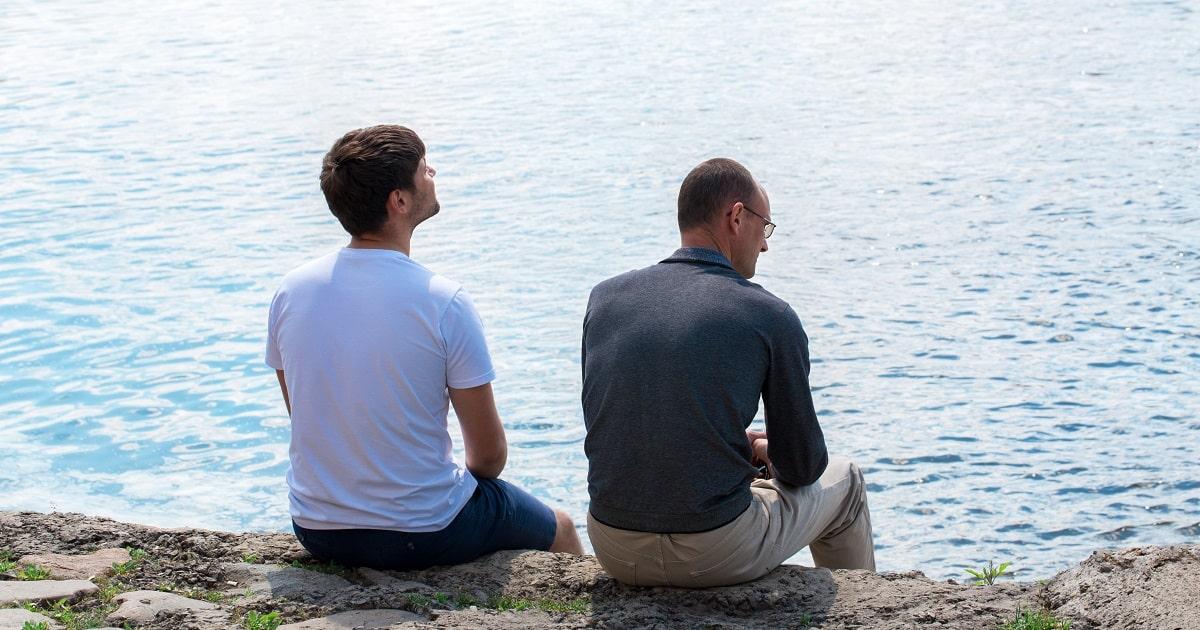 川のそばで恐怖について打ち明け合うふたりの男性