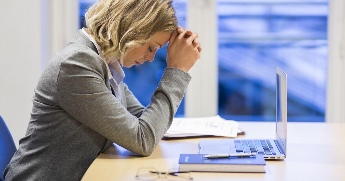ストレスと頭痛を抱えるビジネスパーソン