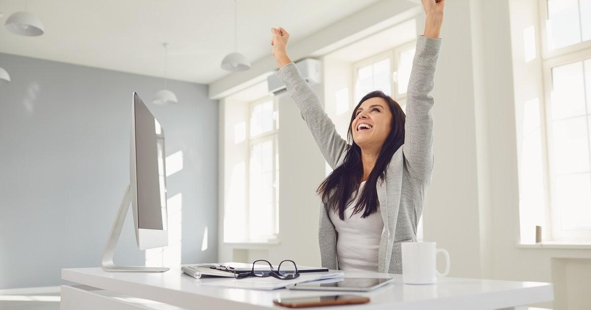 「やったー!」と明るい職場のデスクで万歳&ガッツポーズをとる女性