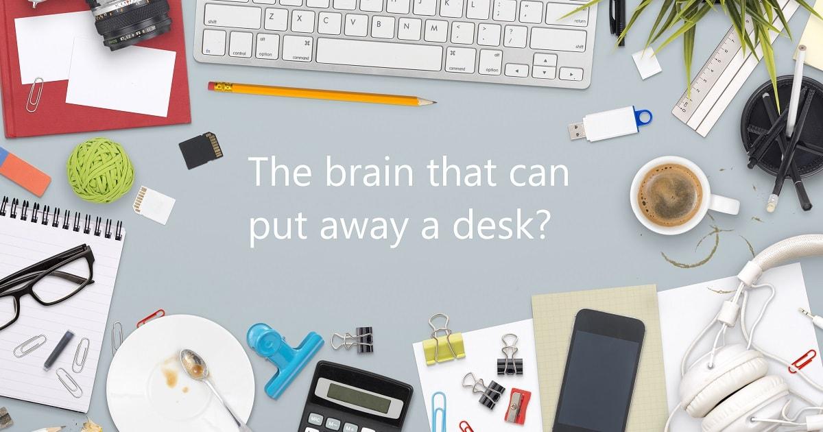 オフィスの散らかった机と「片づけられる脳?」の文字