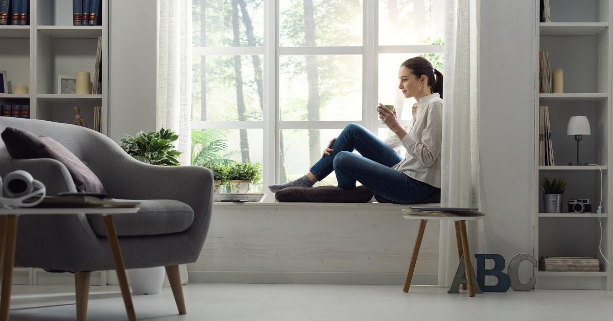 窓辺でリラックスしながらコーヒーを飲む女性