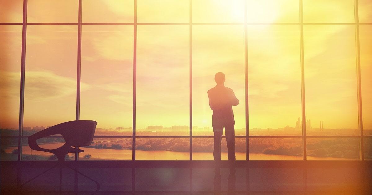 広いオフィスの大きな窓から夕焼け色になった景色を眺めるCEO