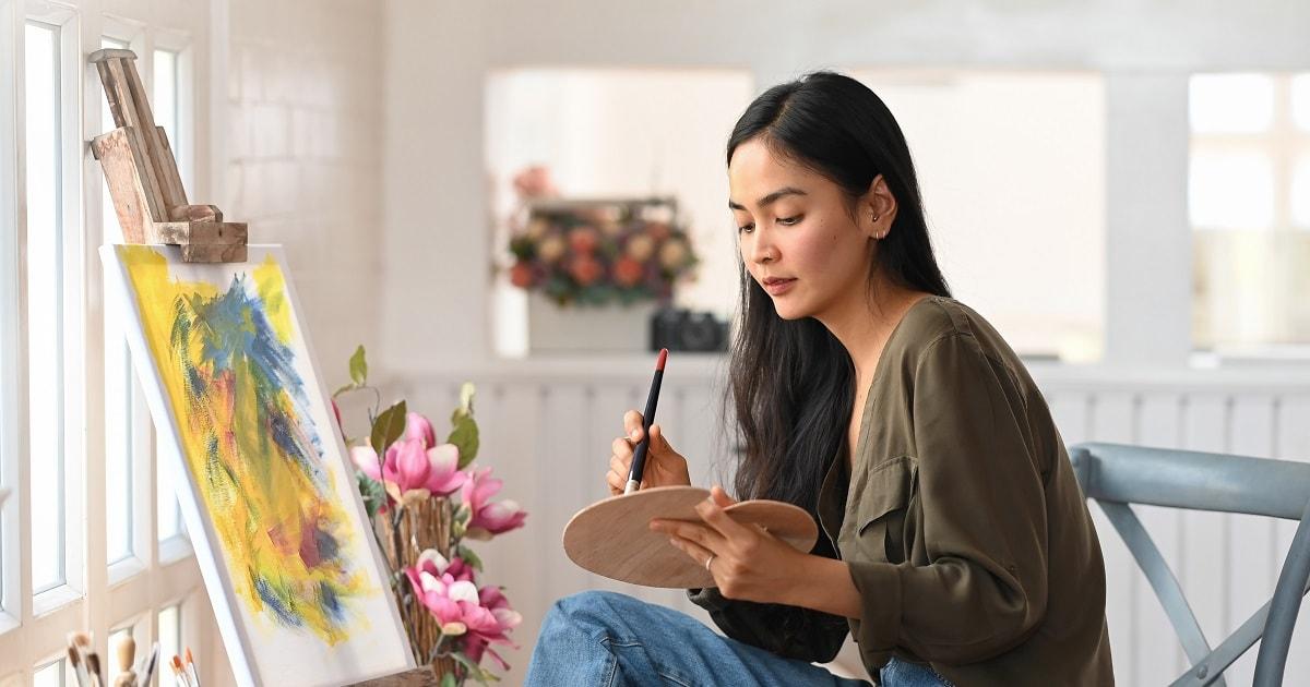 自宅、リラックスした表情で絵を描く女性