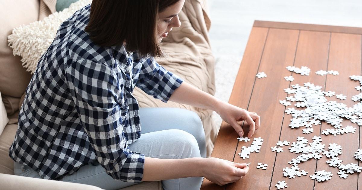 自宅でジグソーパズルを行う若い女性