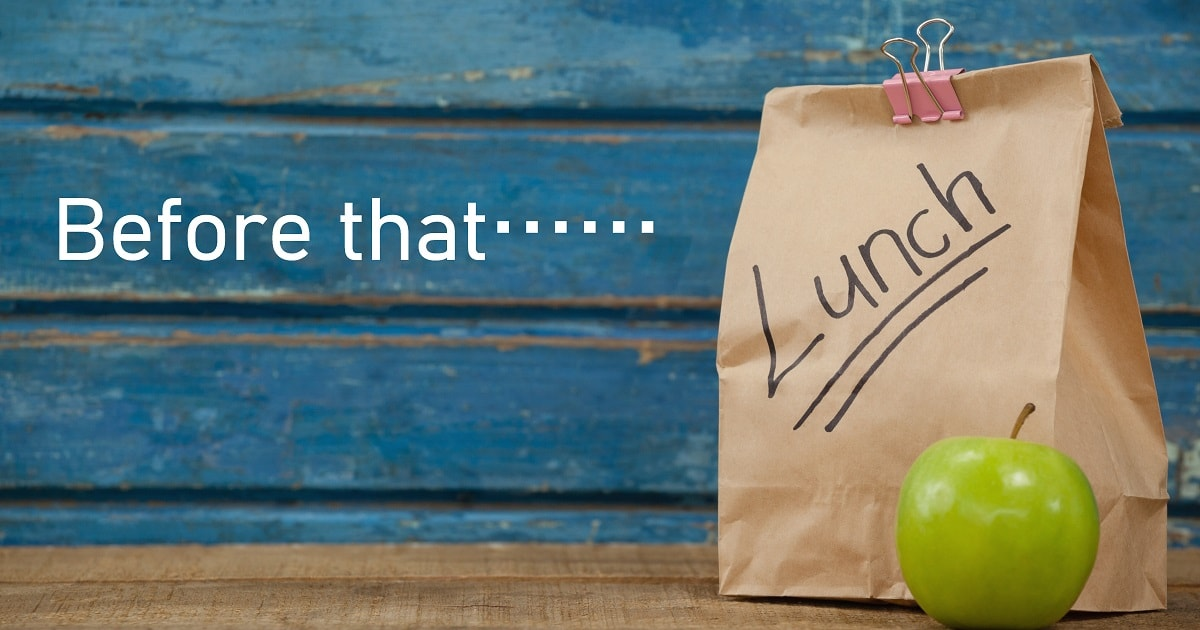 ランチが入った茶色い袋と青りんご