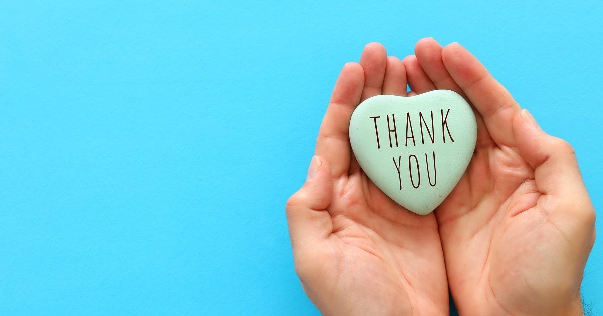 ブルーのバックに「Thank you」と書かれたブルーのハートをもつ手