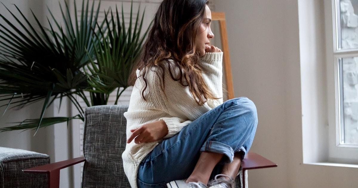 傷つきやすい女性、家のソファーで