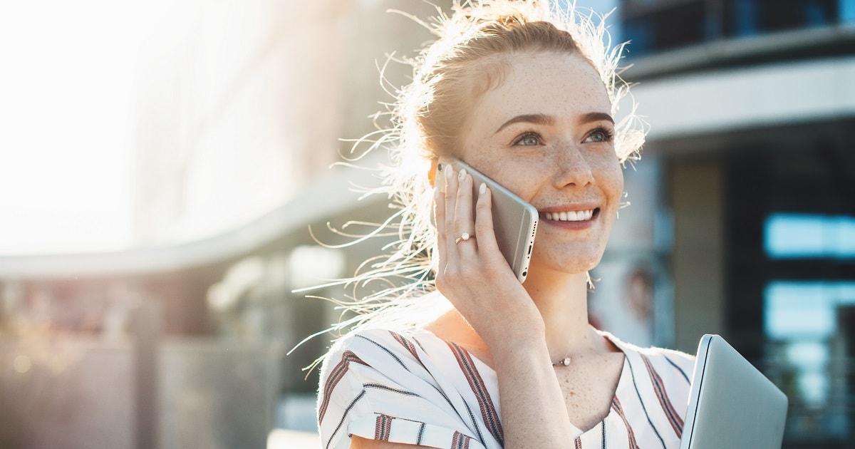 晴れた日に清々しい表情で仕事の電話をする女性