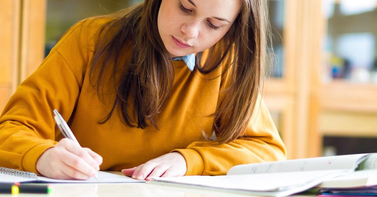 キャメル色のセーターを着た若い女性が勉強している様子