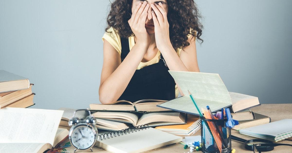 勉強中に考え込んでいる女子学生