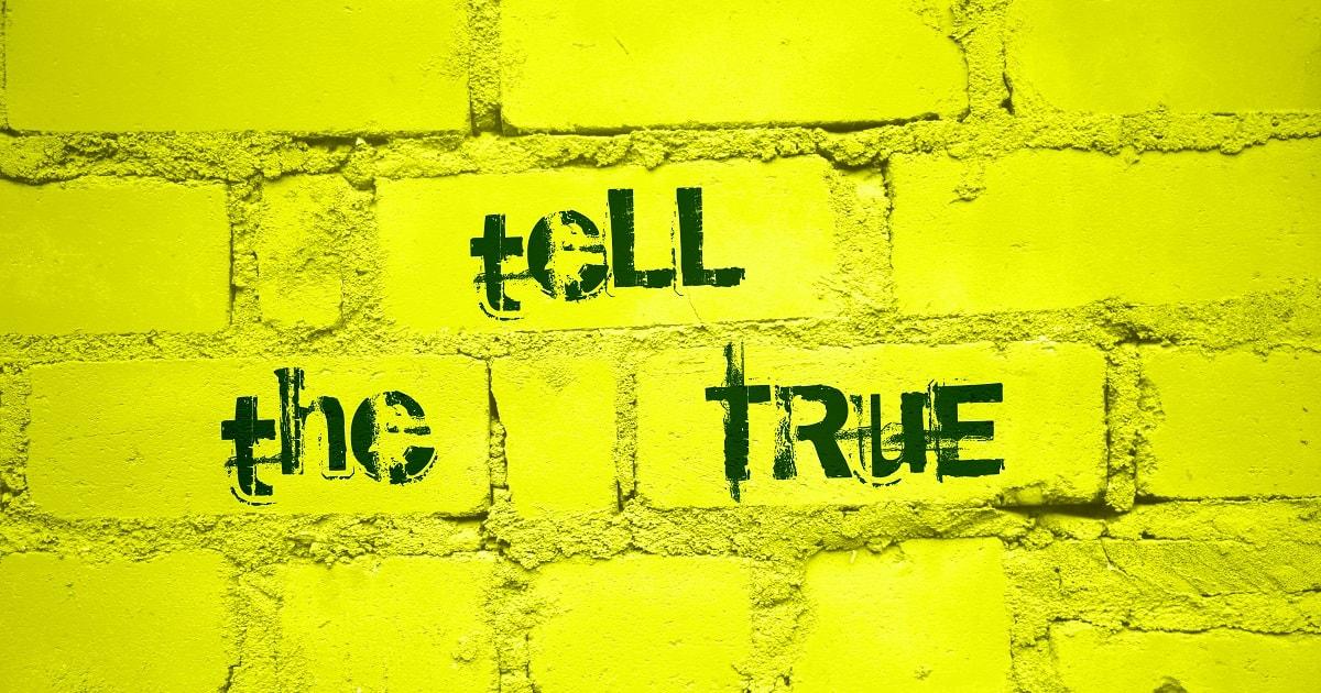黄色い壁に書かれた「本当のことを言ってください」という文字