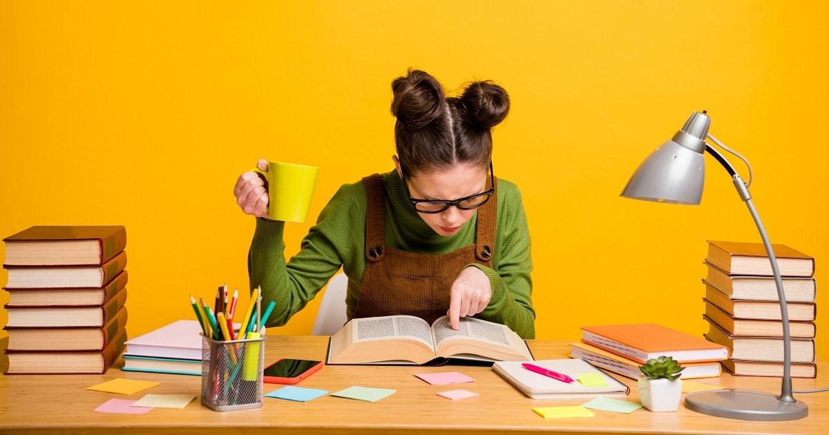 黄色い背景、熱心に勉強する若い女性