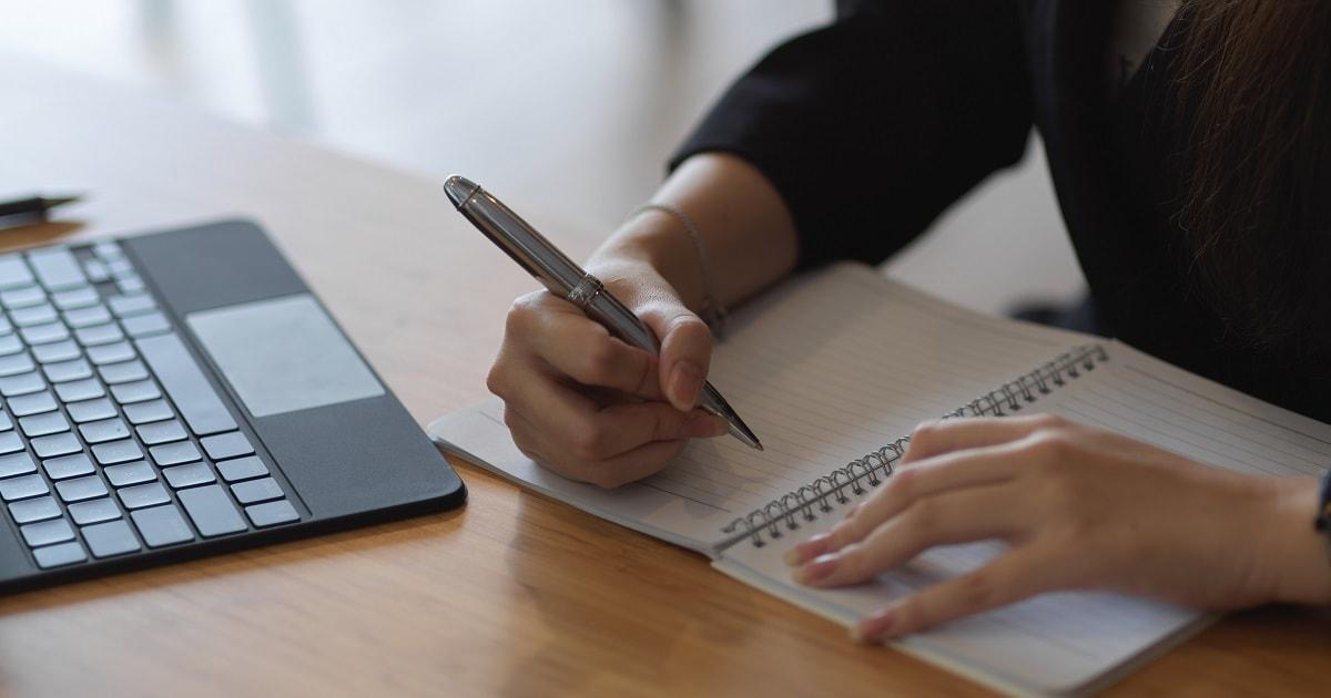 紙のノートに何かを書こうとしている女性、ビジネスパーソン