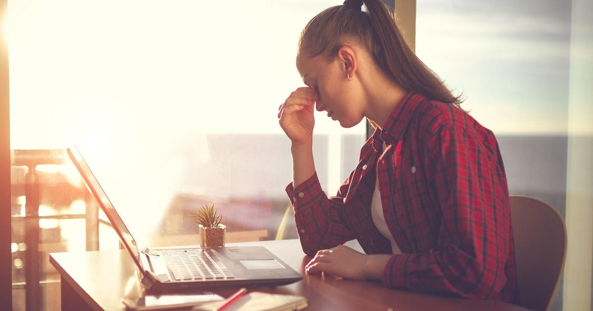 目が疲れてきた様子の、ノートパソコンで作業するチェックのシャツを着た女性