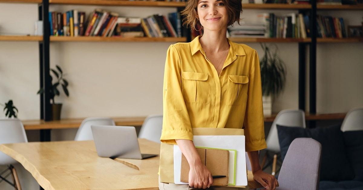 ノートや手帳などを手にオフィスでほほ笑む、黄色いシャツを着た女性